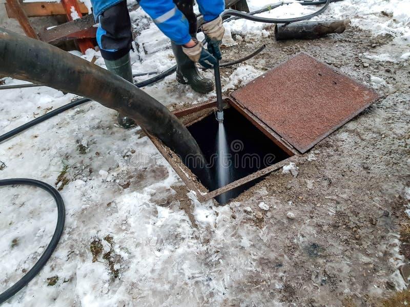 Εργαζόμενος που καθαρίζει τη σηπτική δεξαμενή με το νερό μετά από να εκκενώσει από τα καθαρότερα μηχανήματα λυμάτων στοκ εικόνα με δικαίωμα ελεύθερης χρήσης