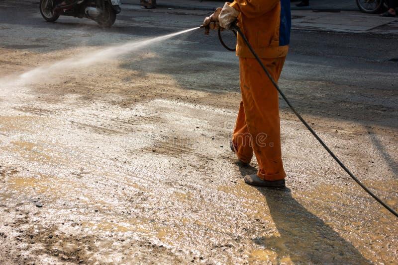 Εργαζόμενος που καθιστά την οδό υγρή με τον ψεκασμό νερού στην περιοχή κατασκευής στοκ φωτογραφίες