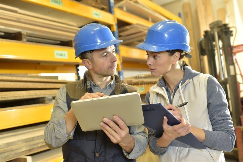 Εργαζόμενος που μιλά στο overseer στην αποθήκη εμπορευμάτων στοκ εικόνα με δικαίωμα ελεύθερης χρήσης