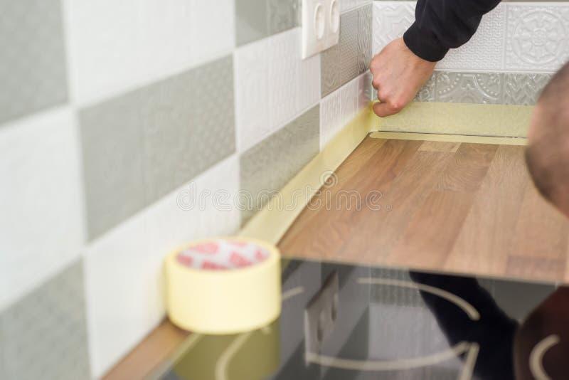 Εργαζόμενος που προστατεύει countertop στην κουζίνα με την καλύπτοντας ταινία πρίν αρχίζει τις επισκευές κατασκευής με τα κεραμικ στοκ εικόνες