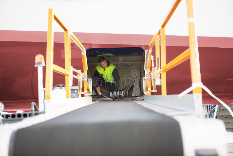 Εργαζόμενος που σκύβει στο αεροπλάνο με το μεταφορέα αποσκευών στο πρώτο πλάνο στοκ φωτογραφίες με δικαίωμα ελεύθερης χρήσης