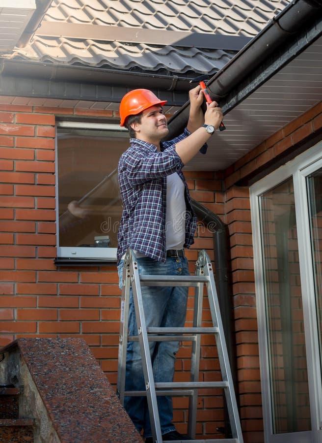 Εργαζόμενος που στέκεται στη σκάλα βημάτων και που επισκευάζει την υδρορροή στο σπίτι στοκ εικόνες με δικαίωμα ελεύθερης χρήσης