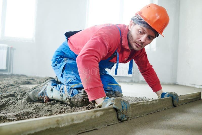 Εργαζόμενος που το εσωτερικό πάτωμα τσιμέντου με το κατεβατό απεικόνιση αποθεμάτων
