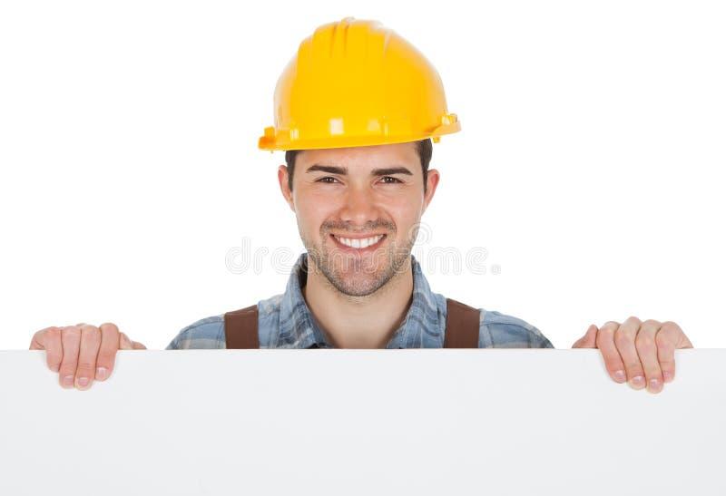 Εργαζόμενος που φορά το σκληρό καπέλο και που κρατά το κενό έμβλημα στοκ εικόνα