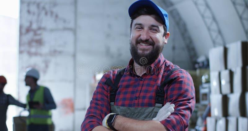 Εργαζόμενος που χαμογελά στη κάμερα σε μια αποθήκη εμπορευμάτων στοκ εικόνα