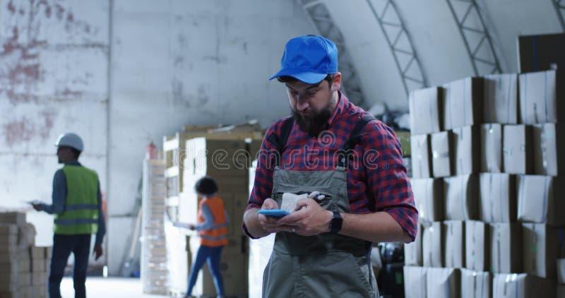 Εργαζόμενος που χρησιμοποιεί το τηλέφωνο σε μια αποθήκη εμπορευμάτων στοκ φωτογραφία
