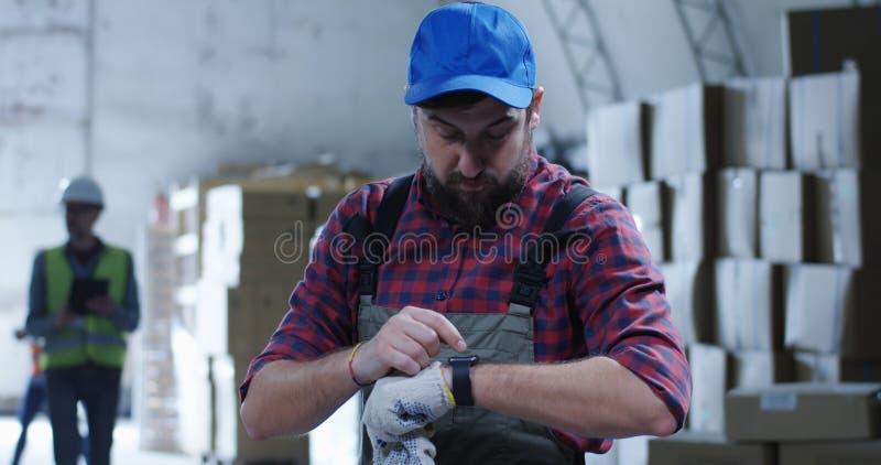 Εργαζόμενος που χρησιμοποιεί το τηλέφωνο σε μια αποθήκη εμπορευμάτων στοκ εικόνες με δικαίωμα ελεύθερης χρήσης