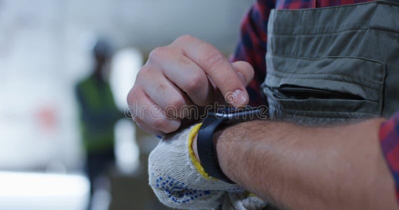 Εργαζόμενος που χρησιμοποιεί smartwatch σε μια αποθήκη εμπορευμάτων στοκ φωτογραφίες με δικαίωμα ελεύθερης χρήσης