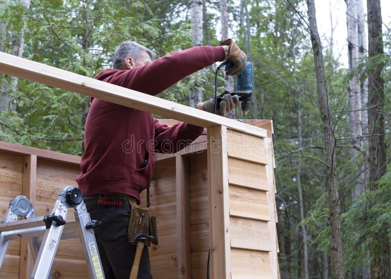 Εργαζόμενος που χτίζει το υπόστεγο αποθήκευσης DIY στοκ φωτογραφίες
