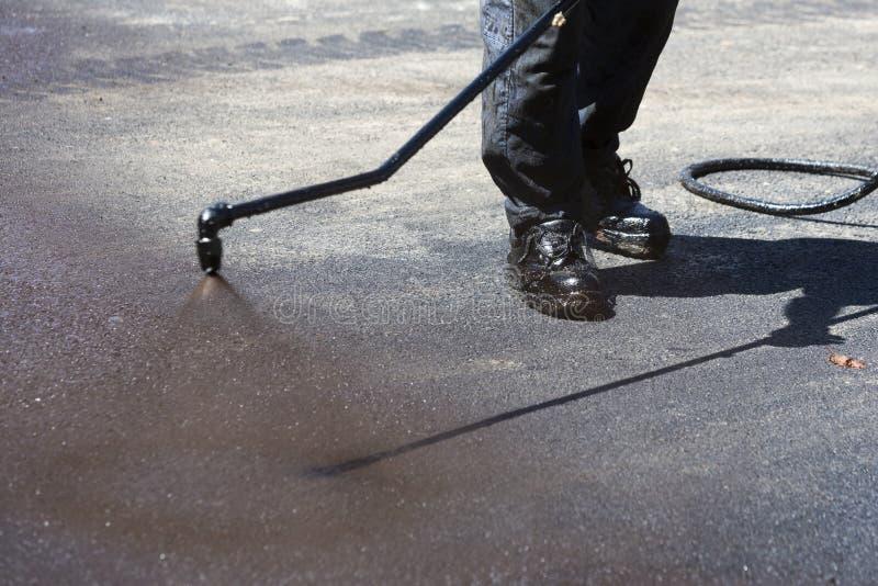 Εργαζόμενος που ψεκάζει την καυτή άσφαλτο στοκ φωτογραφίες με δικαίωμα ελεύθερης χρήσης