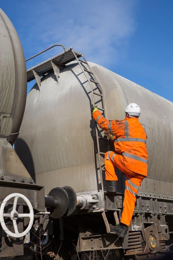 Εργαζόμενος σιδηροδρόμων που αναρριχείται επάνω σε ένα βαγόνι εμπορευμάτων βυτιοφόρων στοκ φωτογραφία