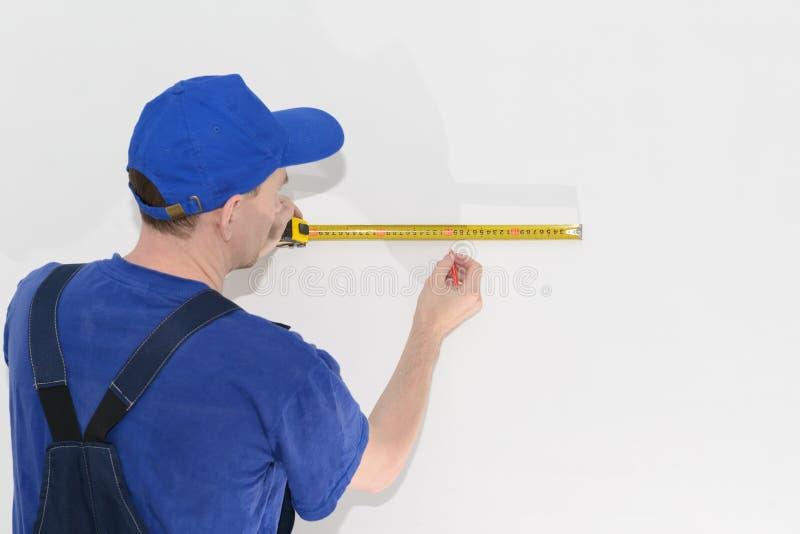 Εργαζόμενος στα μπλε workwear μέτρα η απόσταση που χρησιμοποιεί ένα μέτρο ταινιών στοκ εικόνες