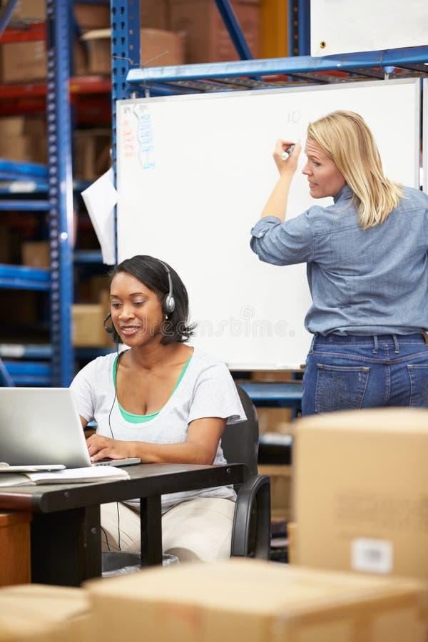 Εργαζόμενος στην αποθήκη εμπορευμάτων που φορά την κάσκα και που χρησιμοποιεί το lap-top στοκ εικόνες