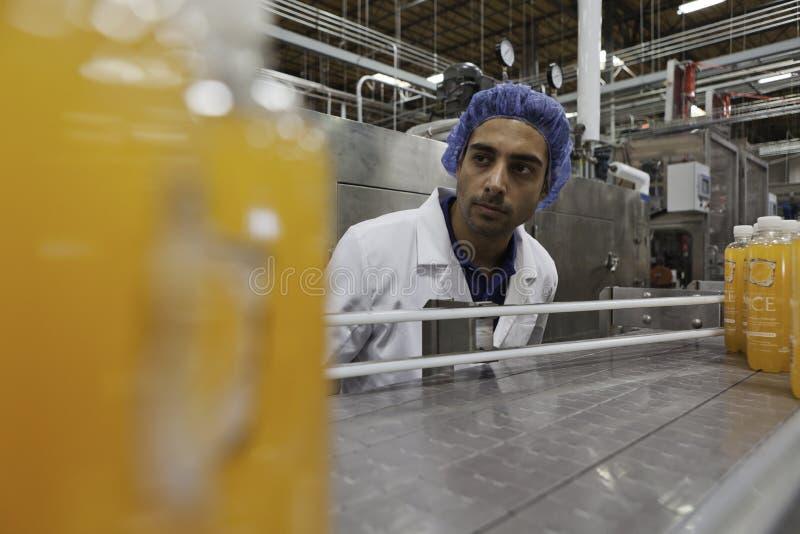 Εργαζόμενος στη γραμμή παραγωγής που κοιτάζει κάτω από τη ζώνη μεταφορέων στοκ εικόνες