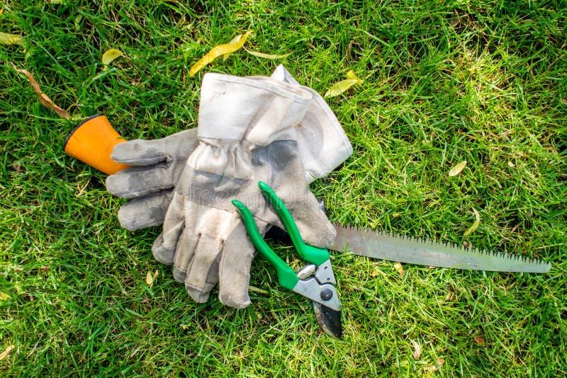 Εργαζόμενος στον κήπο, εργαλεία κήπων που βάζει στην πράσινη χλόη στοκ εικόνες