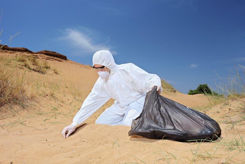 Εργαζόμενος στο προστατευτικό κοστούμι που κρατά μια τσάντα αποβλήτων και που συλλέγει το SAM στοκ εικόνες με δικαίωμα ελεύθερης χρήσης