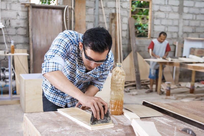 Εργαζόμενος στο χώρο εργασίας ξυλουργών που εφαρμόζει το ξύλινο βινύλιο στο u πινάκων στοκ εικόνες