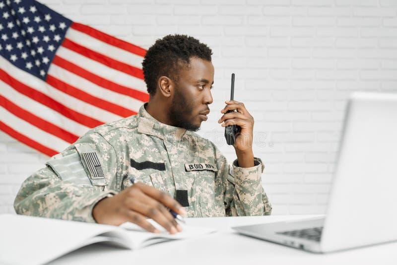Εργαζόμενος των αμερικανικών εγγράφων γραψίματος στρατού, που χρησιμοποιούν το lap-top στοκ εικόνες