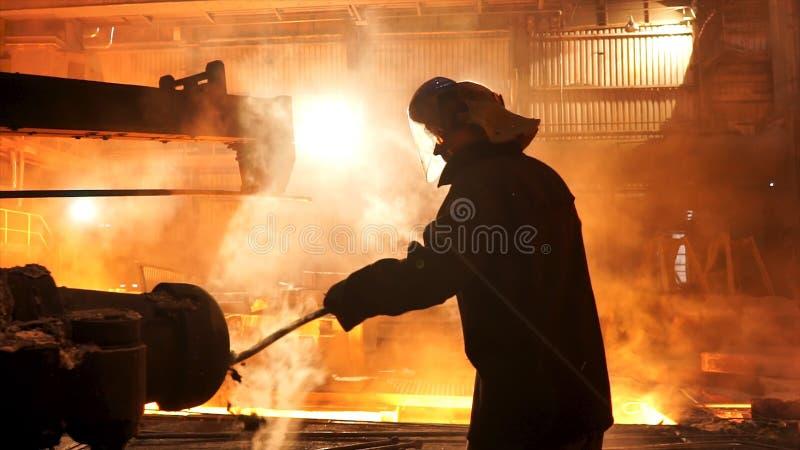 Εργαζόμενος χάλυβα που αφαιρεί τη σκουριά από τον ηλεκτρικό λειώνοντας φούρνο χοανών επαγωγής στις μεταλλουργικές εγκαταστάσεις,  στοκ φωτογραφίες