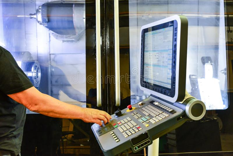 Εργαζόμενος, χειριστής του πίνακα ελέγχου του προγράμματος της λειτουργίας ενός μεγάλης ακρίβειας CNC επεξεργαμένος στη μηχανή κέ στοκ εικόνες