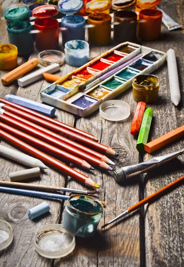Εργαλεία για την έμπνευση καλλιτεχνών που δημιουργεί Αντικείμενα για το σχέδιο Χρώμα, κραγιόνια, μολύβια σε έναν ξύλινο πίνακα στοκ εικόνες