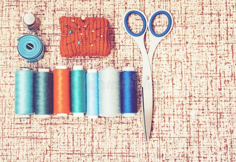 Εργαλεία για τη ραπτική, κόκκινο πλεκτό μαξιλάρι βελόνων για το ράψιμο, ψαλίδι και χρωματισμένες σπείρες νημάτων στο καφετί υπόβα στοκ φωτογραφία με δικαίωμα ελεύθερης χρήσης