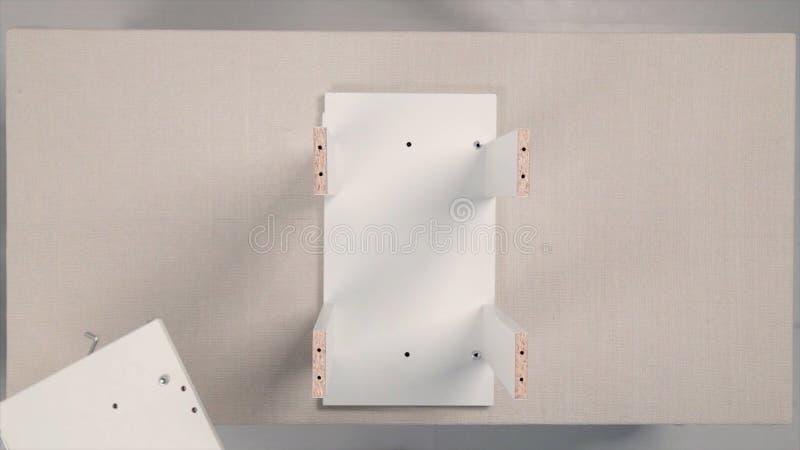 Εργαλεία για τη συνέλευση επίπλων απόθεμα Συγκεντρώνοντας τα έπιπλα, παραδίδει τα γάντια που στενός επάνω σφίγγει τη βίδα επίπλων στοκ φωτογραφία με δικαίωμα ελεύθερης χρήσης