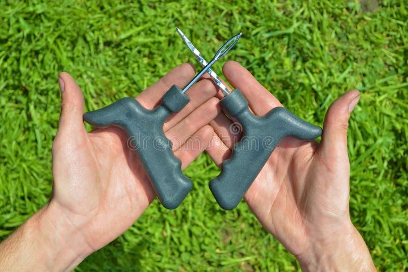 Εργαλεία για τις οπές στις ασωλήνωτες ρόδες μιας μοτοσικλέτας ή ενός αυτοκινήτου, στα βρώμικα χέρια ενός μηχανικού σε μια πράσινη στοκ φωτογραφίες