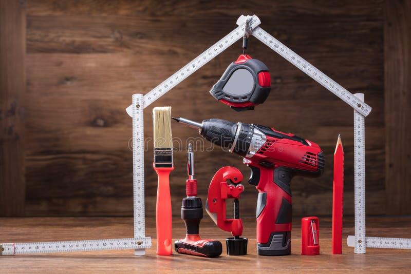 Εργαλεία επισκευών κάτω από το σπίτι που γίνεται με τη μέτρηση της ταινίας στοκ φωτογραφίες