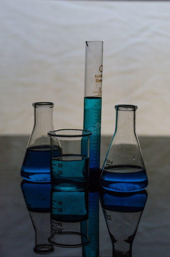 Εργαλεία εργαστηριακών γυαλικών χημείας σε μια απεικονίζοντας επιφάνεια στοκ φωτογραφία