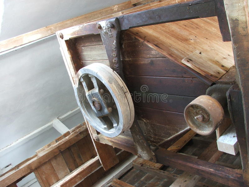 Εργαλεία και τροχαλίες σε ένα παλαιό ξύλινο watermill που χρησιμοποιείται για τη λείανση φ στοκ εικόνα