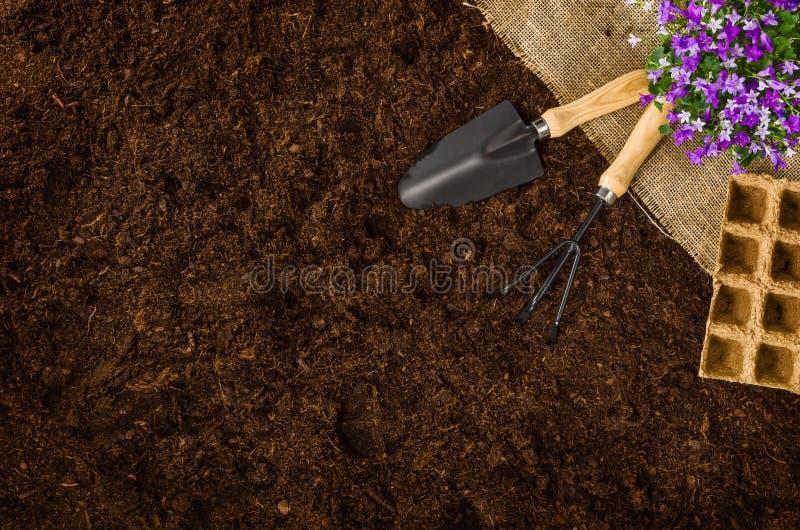 Εργαλεία κηπουρικής στη τοπ άποψη υποβάθρου εδαφολογικής σύστασης κήπων στοκ εικόνα