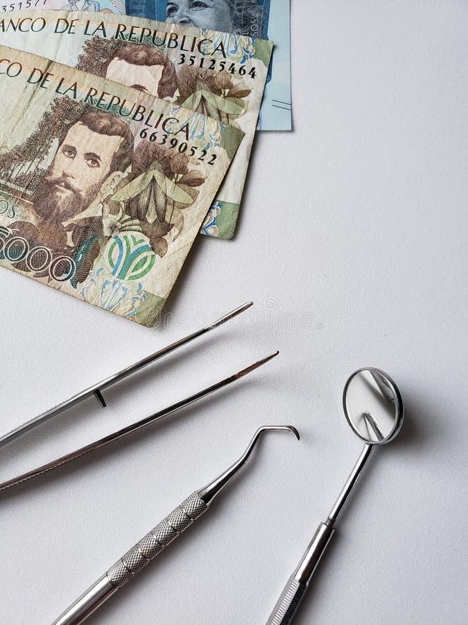 εργαλεία οδοντιάτρων για την προφορική αναθεώρηση και τα κολομβιανά τραπεζογραμμάτια στοκ φωτογραφία με δικαίωμα ελεύθερης χρήσης