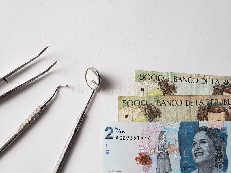 εργαλεία οδοντιάτρων για την προφορική αναθεώρηση και τα κολομβιανά τραπεζογραμμάτια στοκ εικόνες