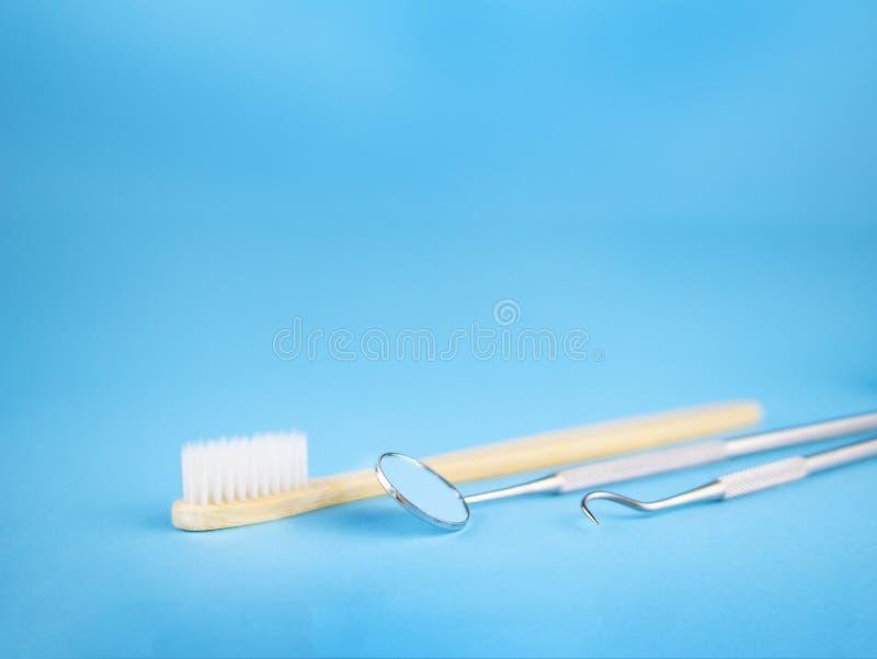 Εργαλεία οδοντιάτρων στο οδοντικό γραφείο: καθρέφτης οδοντιάτρων και γάντζος, άσπρη ξύλινη οδοντόβουρτσα στοκ εικόνες