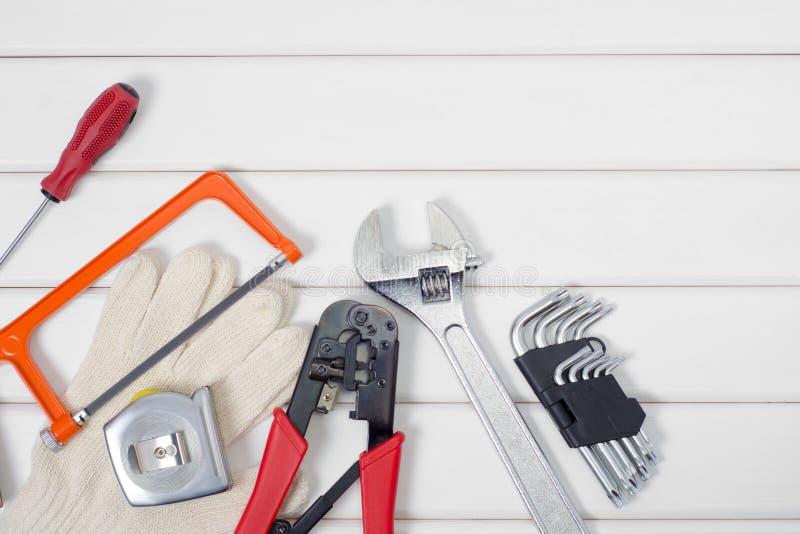 Εργαλεία σε ένα άσπρο ξύλινο υπόβαθρο στοκ εικόνες