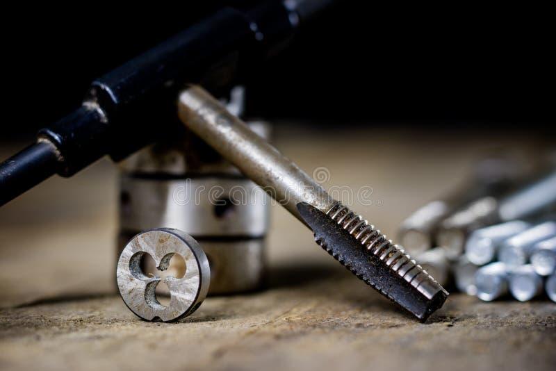 Εργαλεία σιδηρουργείου στον πίνακα εργαστηρίων Πέρασμα κλωστής σε βελόνα των κύβων και των βρυσών ι στοκ φωτογραφία