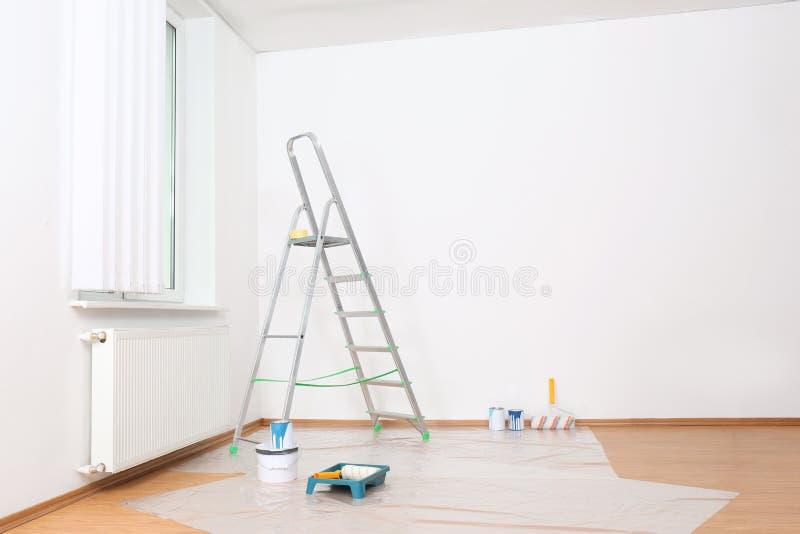 Εργαλεία Stepladder και ζωγραφικής κοντά στο παράθυρο στο κενό άσπρο δωμάτιο στοκ φωτογραφίες