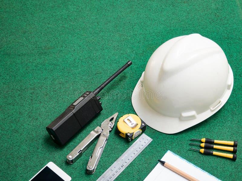 Εργαλείο βιοτεχνών, εξοπλισμός οικοδόμησης για τον εργαζόμενο ατόμων, άσπρο κράνος ασφάλειας, walkie-talkie, φορητός ραδιο πομποδ στοκ εικόνα