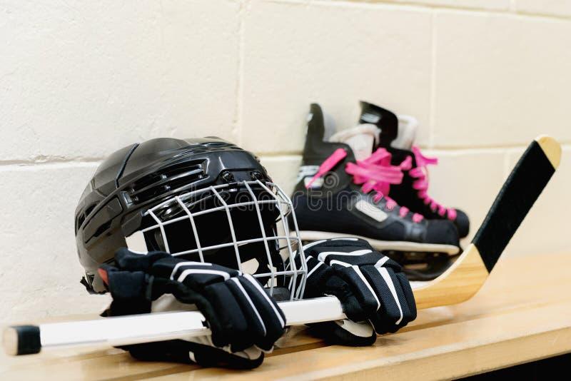 Εργαλείο χόκεϋ κοριτσιών ` s: κράνος, γάντια, ραβδιά, σαλάχια με τις ρόδινες δαντέλλες στοκ φωτογραφία