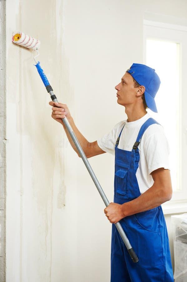 Εργασία ανακαίνισης ζωγράφων στο σπίτι με πρωταρχικό στοκ εικόνες