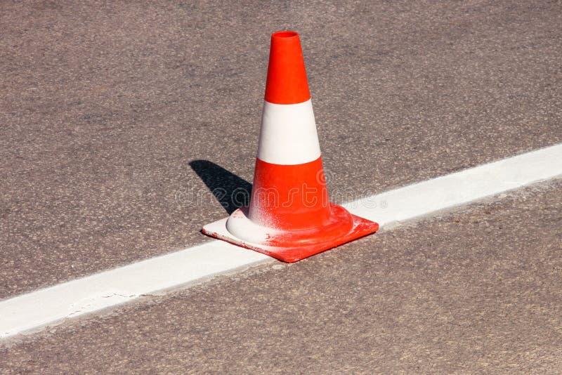 Εργασία για το δρόμο Κώνος κατασκευής Κώνος κυκλοφορίας, με τα άσπρα και πορτοκαλιά λωρίδες στην άσφαλτο Σημάδια οδών και κυκλοφο στοκ φωτογραφία