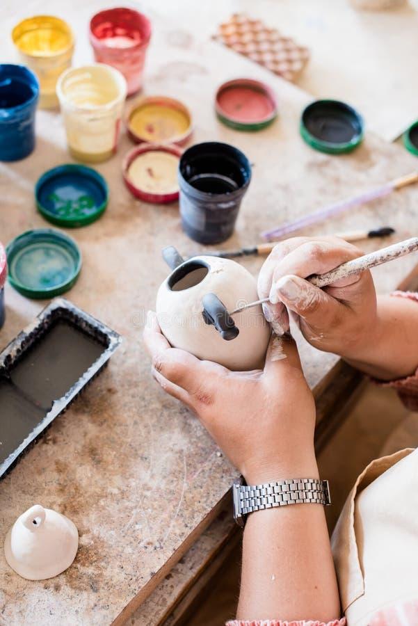 Εργασία γυναικείων η κεραμική καλλιτεχνών στο εσωτερικό στούντιό της, ζωγραφική χεριών της γυναίκας αντιτίθεται στοκ φωτογραφία με δικαίωμα ελεύθερης χρήσης