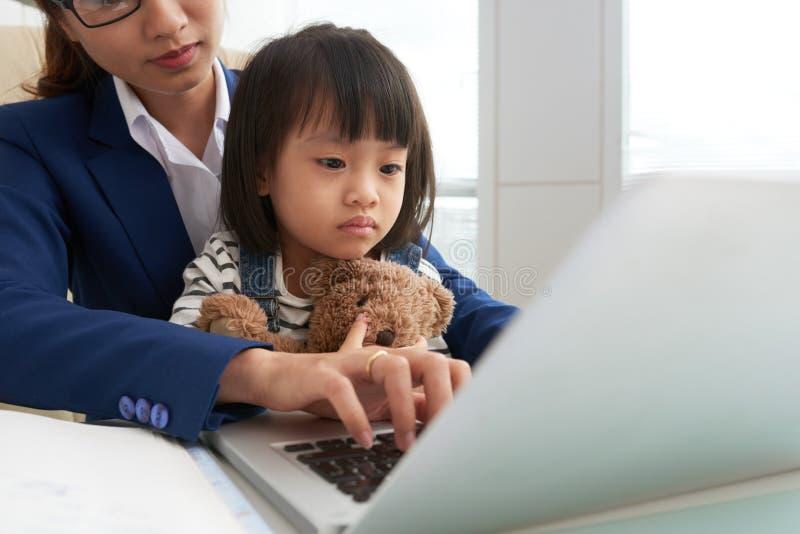 Εργασία γυναικών στην αρχή με το παιδί στοκ εικόνα