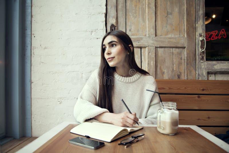 Εργασία γυναικών στον καφέ με το lap-top κοντά στο παράθυρο με τον καφέ latte στοκ φωτογραφία με δικαίωμα ελεύθερης χρήσης
