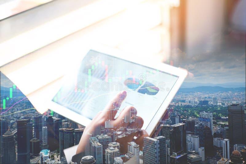 Εργασία επιχειρησιακών γυναικών στην αρχή με τον έλεγχο της επιχειρησιακής έκθεσης σε μια ταμπλέτα/τη χρησιμοποίηση ενός υπολογισ στοκ φωτογραφίες