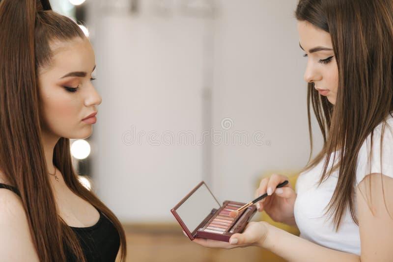 Εργασία καλλιτεχνών Makeup στο στούντιο ομορφιάς της Να ισχύσει γυναικών από τον επαγγελματία αποτελεί τον κύριο Όμορφος αποτελέσ στοκ φωτογραφία με δικαίωμα ελεύθερης χρήσης