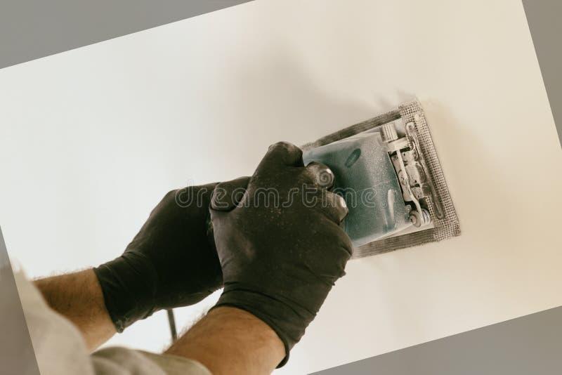 Εργασία λήξης - ο κύριος ευθυγραμμίζει τον τοίχο με sander, έχει τη σκόνη στην οποία λειτουργεί υπάρχει tanirovanie στοκ φωτογραφίες με δικαίωμα ελεύθερης χρήσης