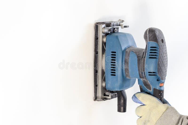 Εργασία λήξης - ο κύριος ευθυγραμμίζει τον τοίχο με sander, έχει τη σκόνη στην οποία λειτουργεί υπάρχει tanirovanie στοκ εικόνα