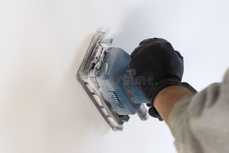 Εργασία λήξης - ο κύριος ευθυγραμμίζει τον τοίχο με sander, έχει τη σκόνη στην οποία λειτουργεί υπάρχει tanirovanie στοκ εικόνες